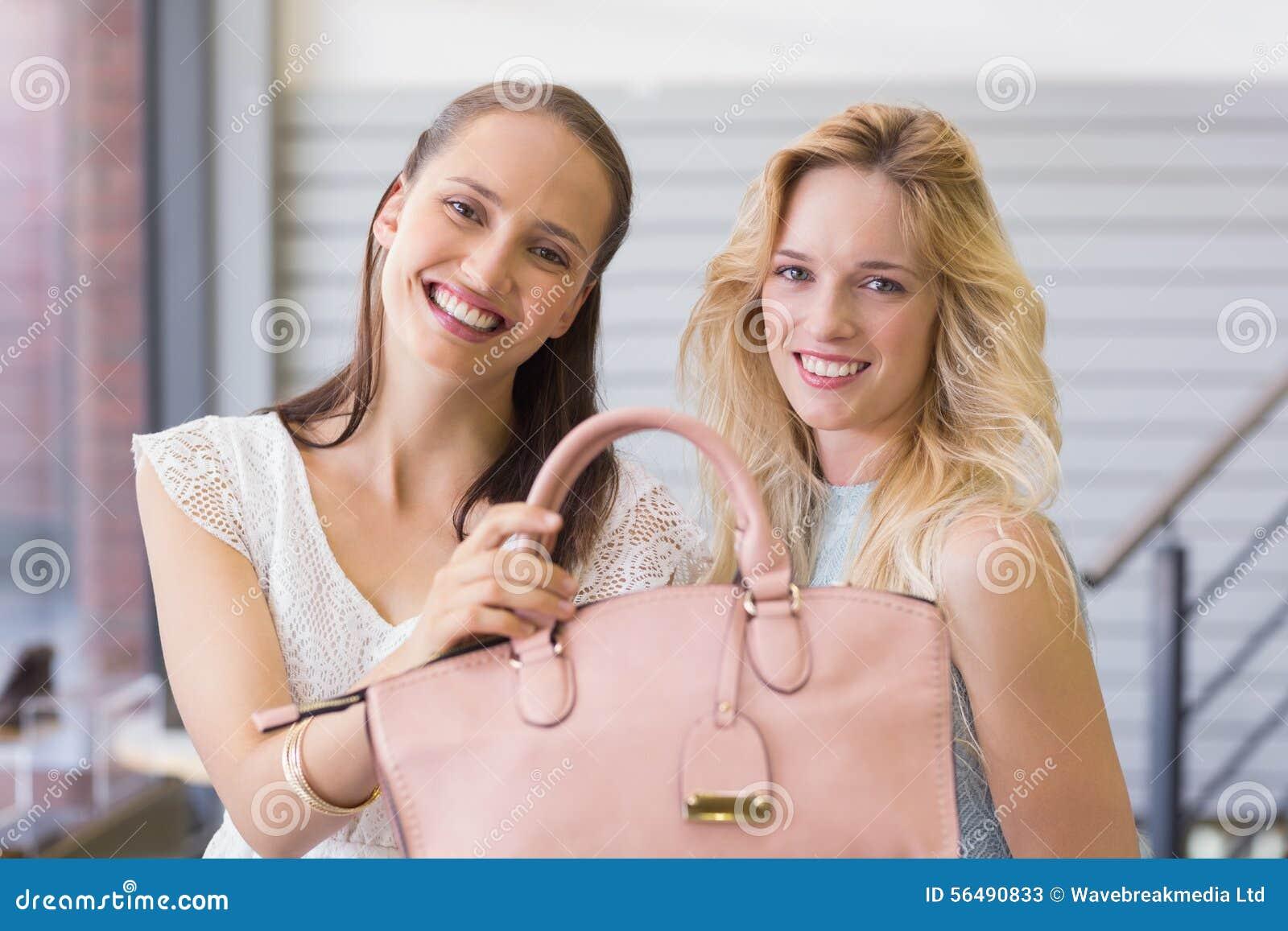 Femmes heureuses souriant à l appareil-photo et tenant un sac à main