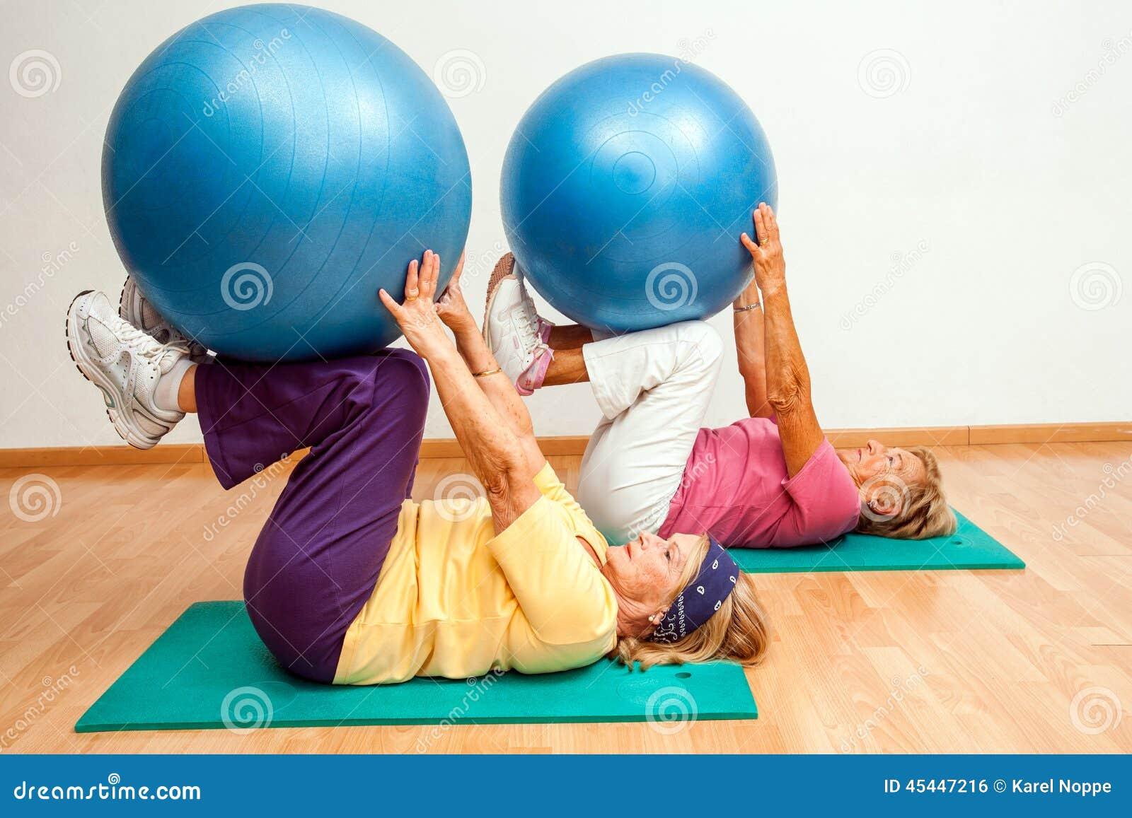 Femmes supérieures s exerçant avec des boules de gymnase