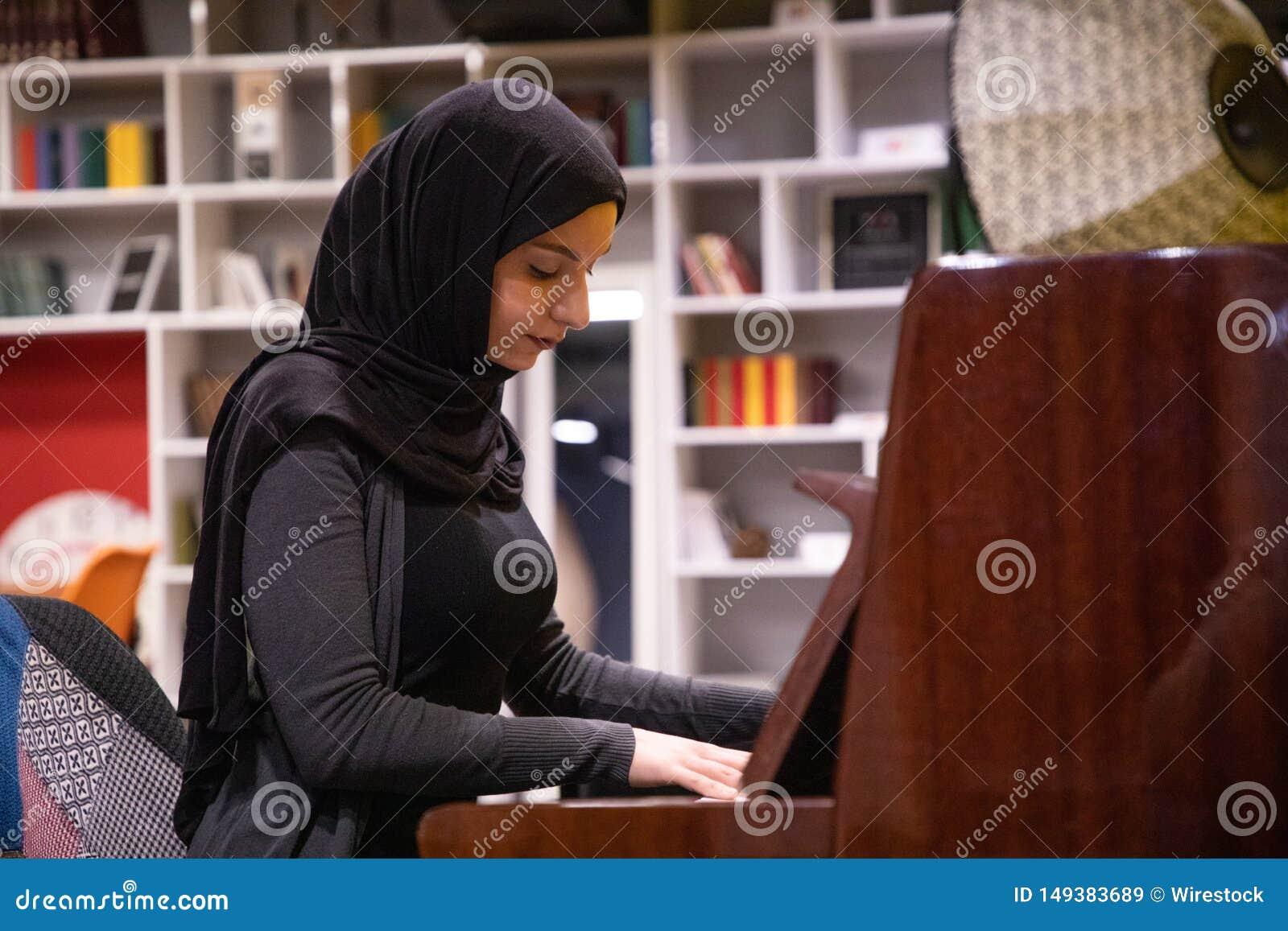 Femmina musulmana attraente in un hijab che gioca piano