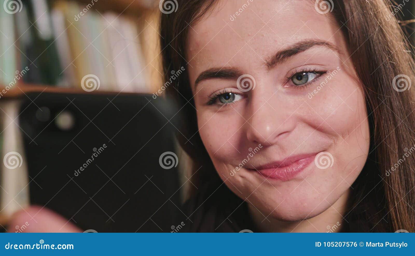 Femmina sorridente che per mezzo del telefono