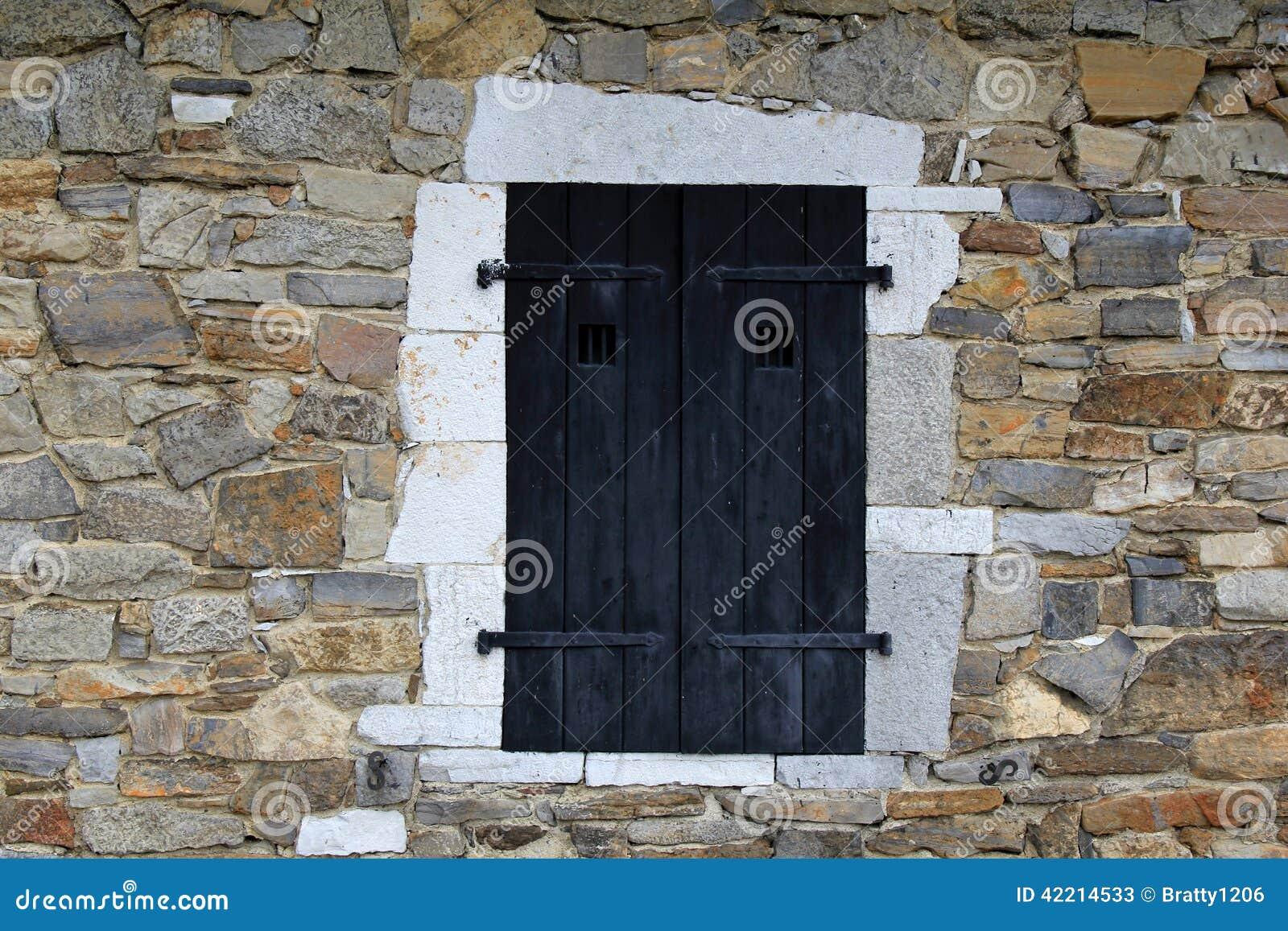 Fen tre volets noire dans le mur en pierre du b timent for Fenetre qui rentre dans le mur