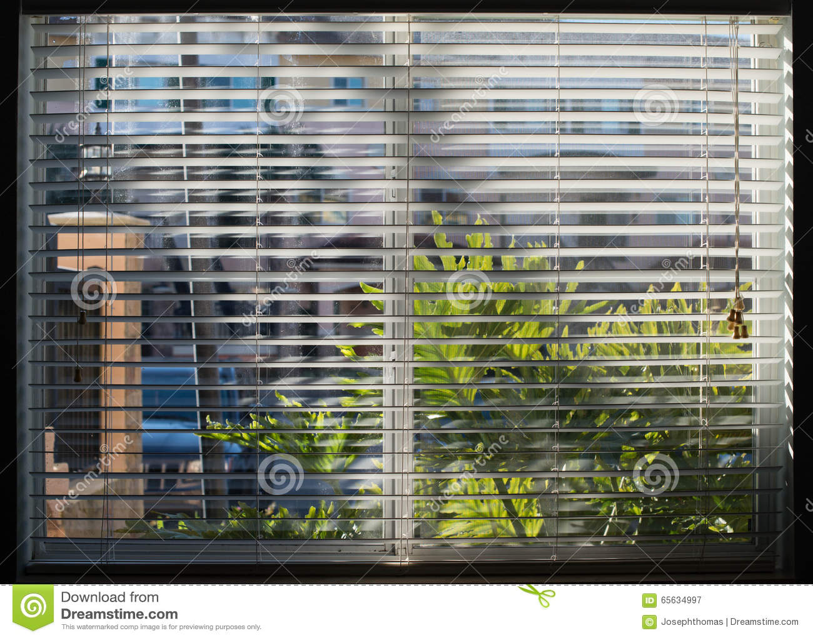 Fenêtre éclaboussée par soleil par les abat-jour blancs