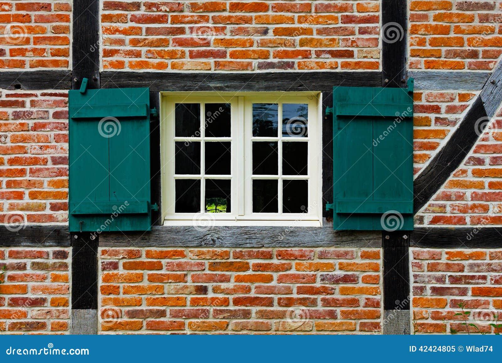 Fen tre avec des volets dans le mur de briques de la for Fenetre maison