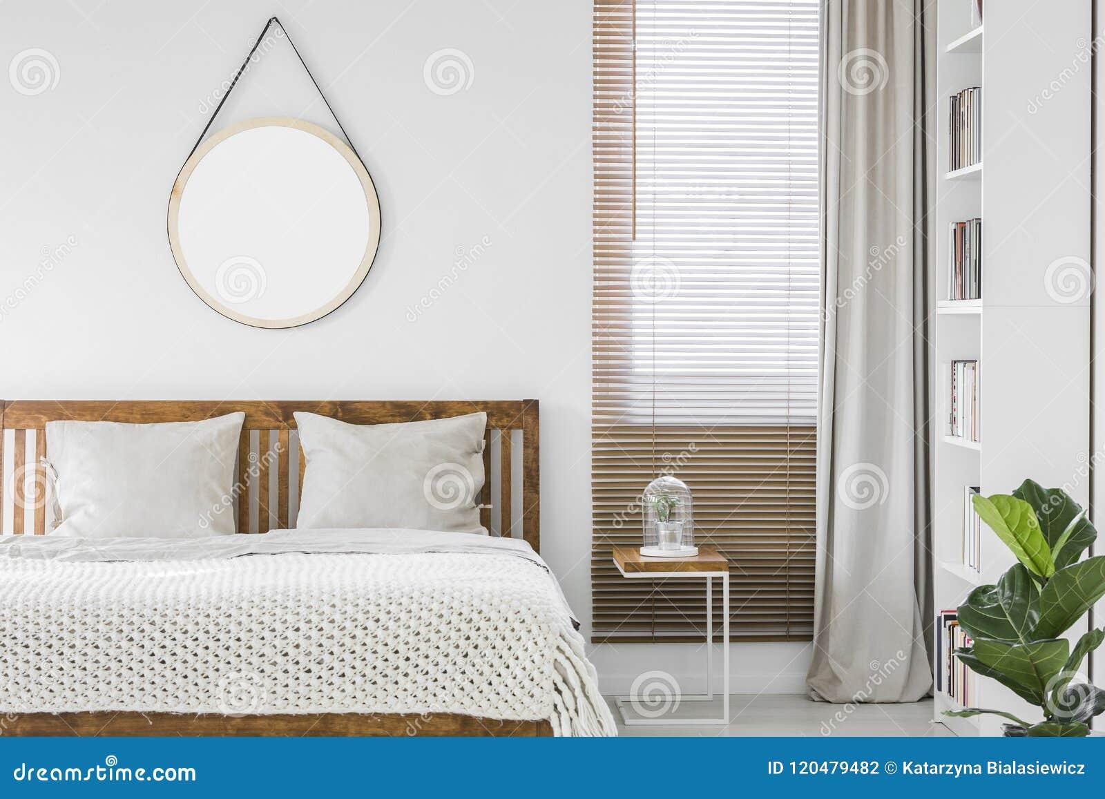 Fenêtre avec les abat-jour en bois et rideau gris-clair dans le bedroo blanc