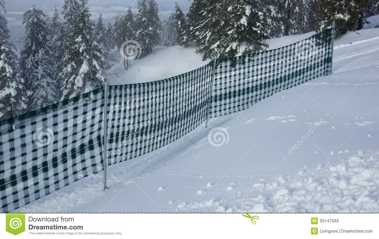 Fence in the snow and fir trees away stock photo image