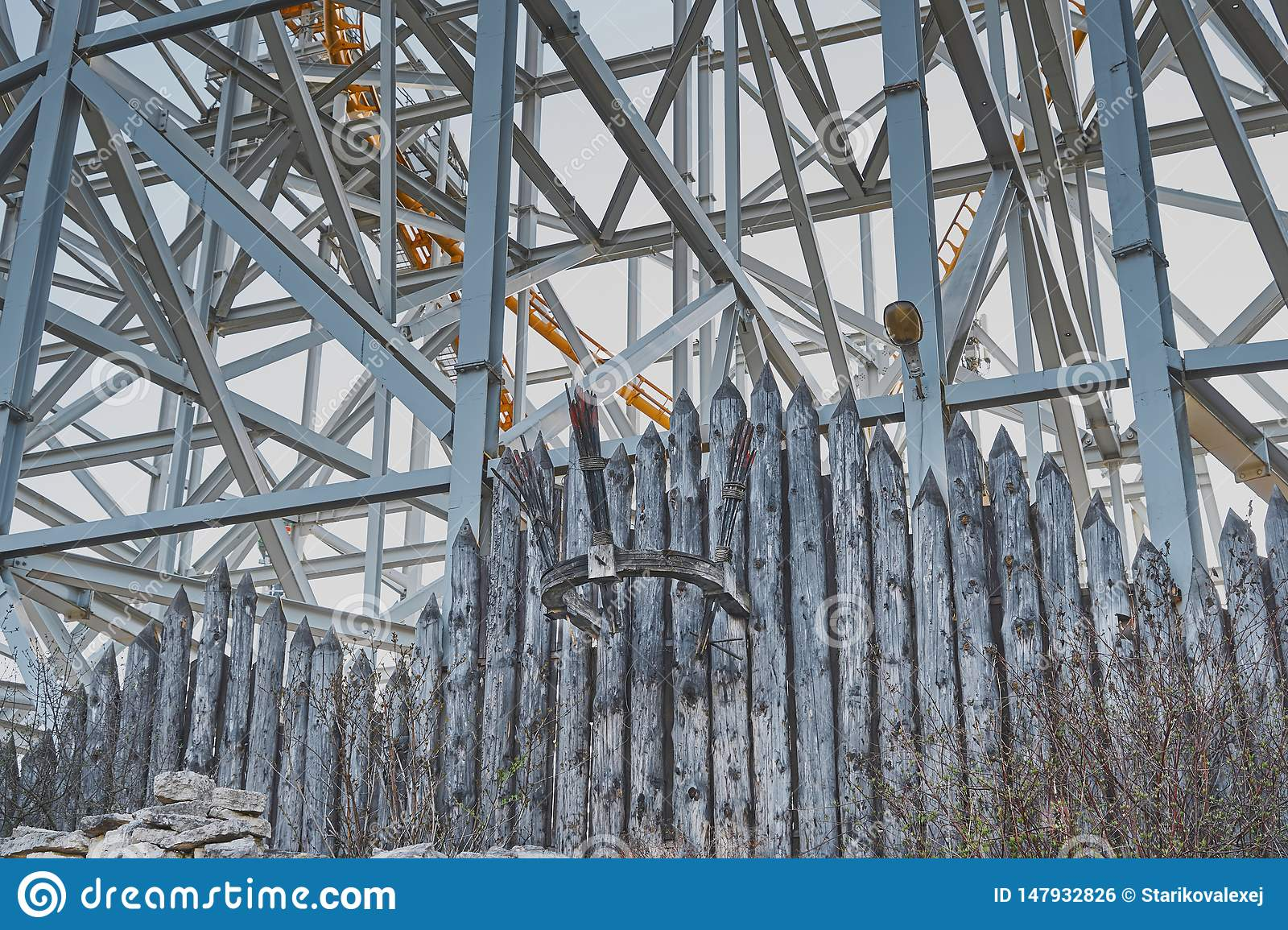 The fence of wooden logs, metal pillar, coniferous trees.