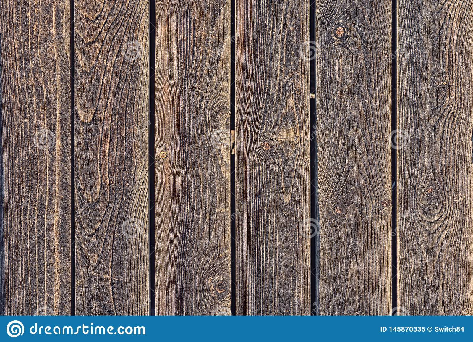 A fence of wooden planks. Background with texture of old wood. Photo for layouts.