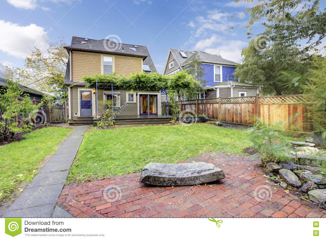 fenced backyard with lawn covered walkway and open terrace stock