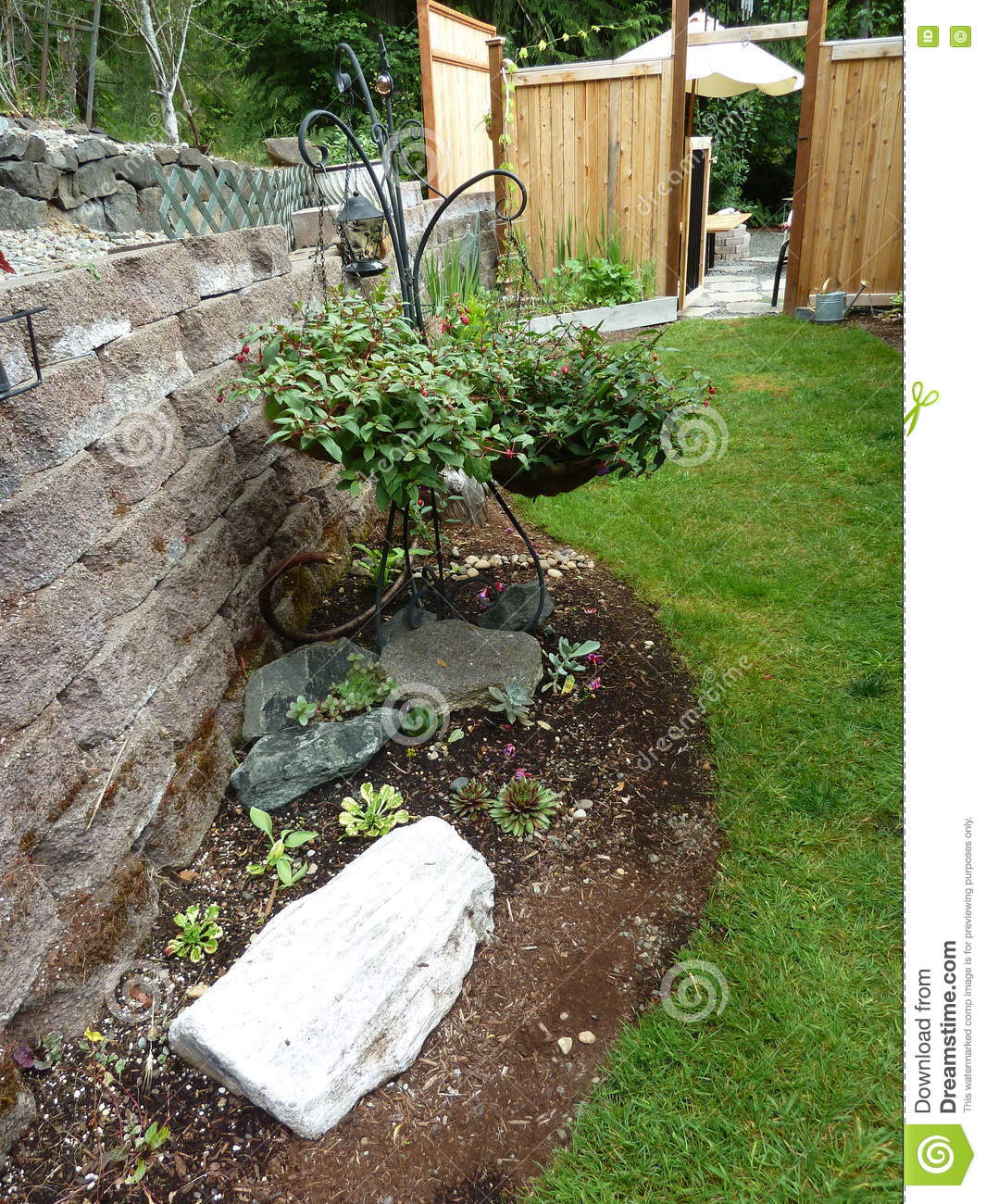 Fenced In Garden With Stone Block Wall In Late Summer