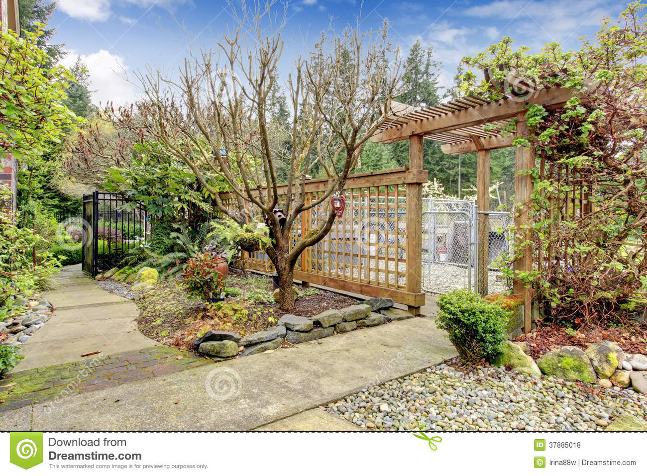 Fenced walkway with trees and flower bed