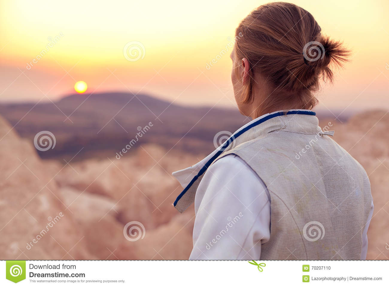 Fencer man on the rocky background and looking forward to the sun goes down