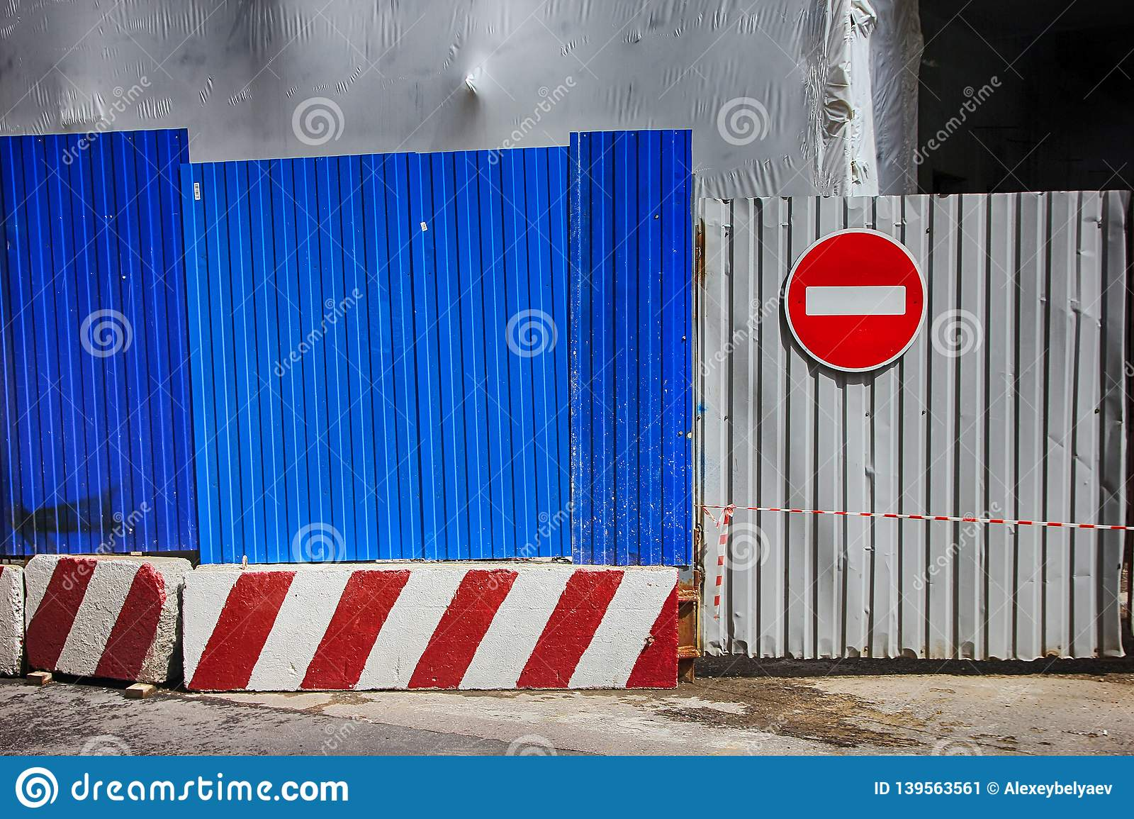 Fencing of construction site with red construction light on the background of blue profiled sheet fence and stop sign