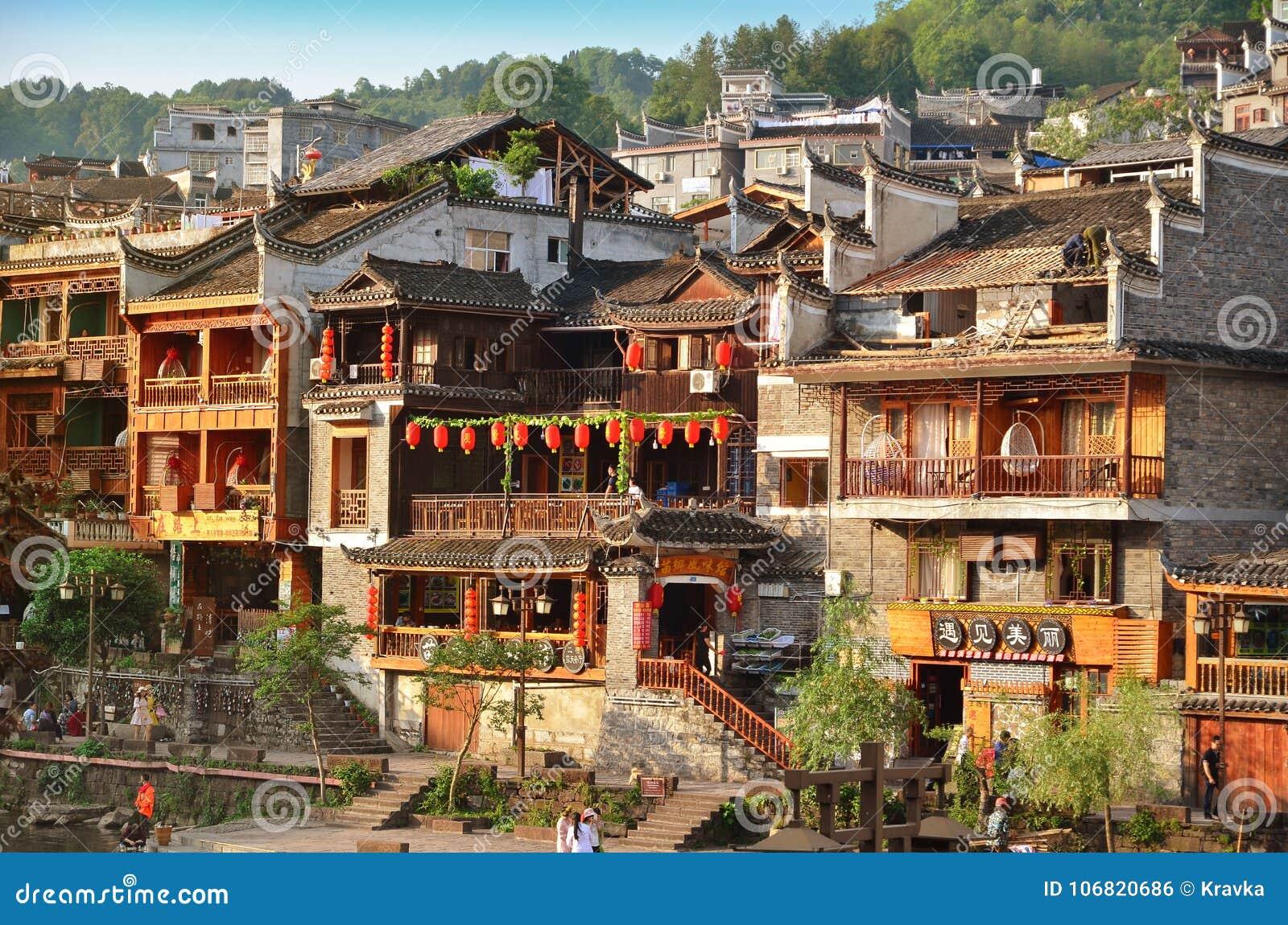 Fenghuang, Chine - 15 mai 2017 : Vieux bâtiment avec des personnes à l espace restauration sur la rive près de Phoenix Hong Bridg