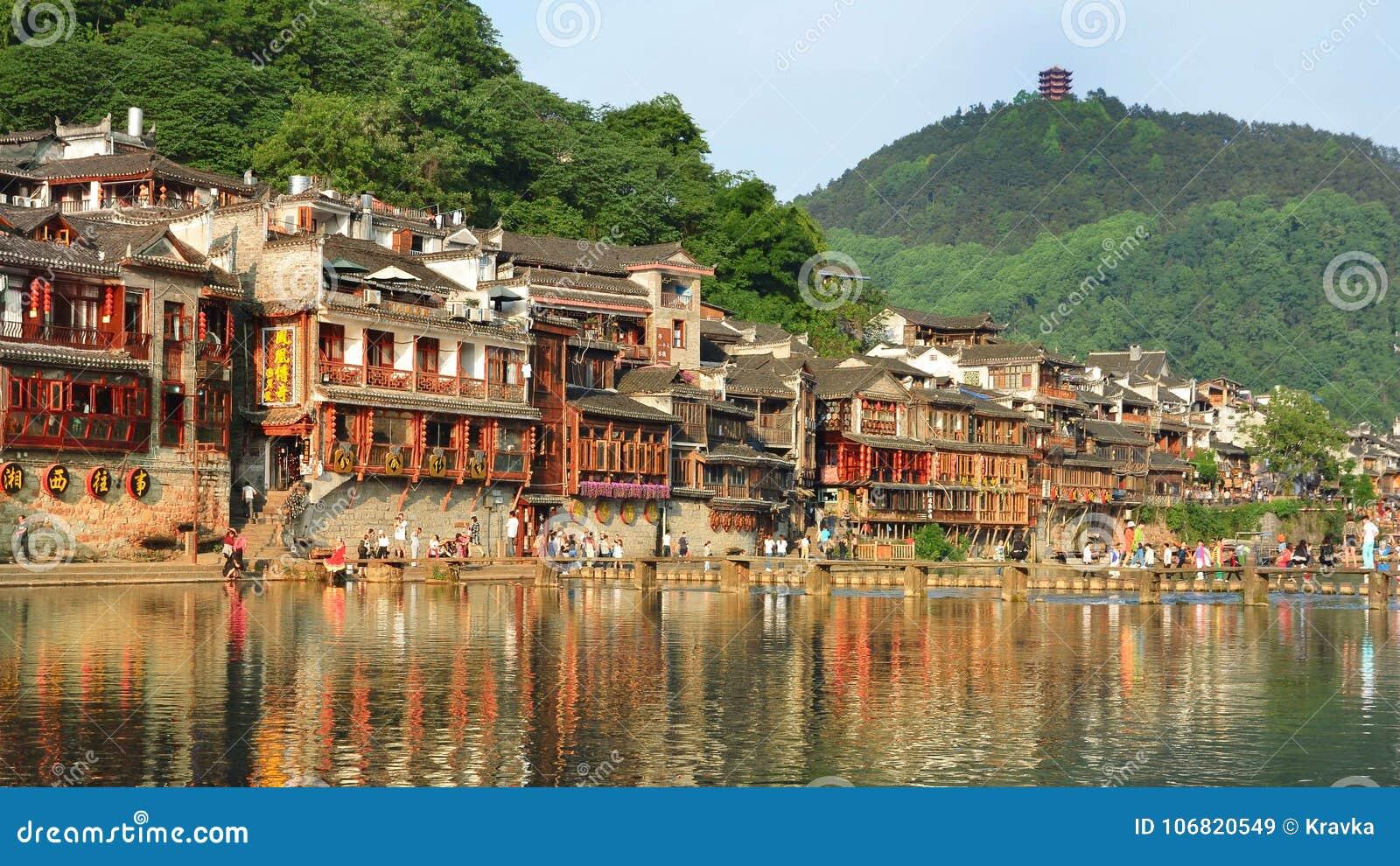 Fenghuang Kina - Maj 15, 2017: Gammal byggnad med folk i matdomstol på flodstranden nära Phoenix Hong Bridge i Fenghuang