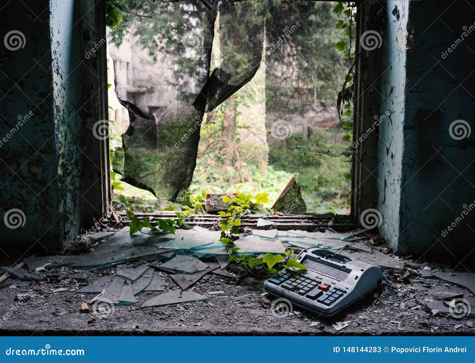 Fenster zerstört in verlassenem Gebäude mit Efeu und einer defekten Registrierkasse