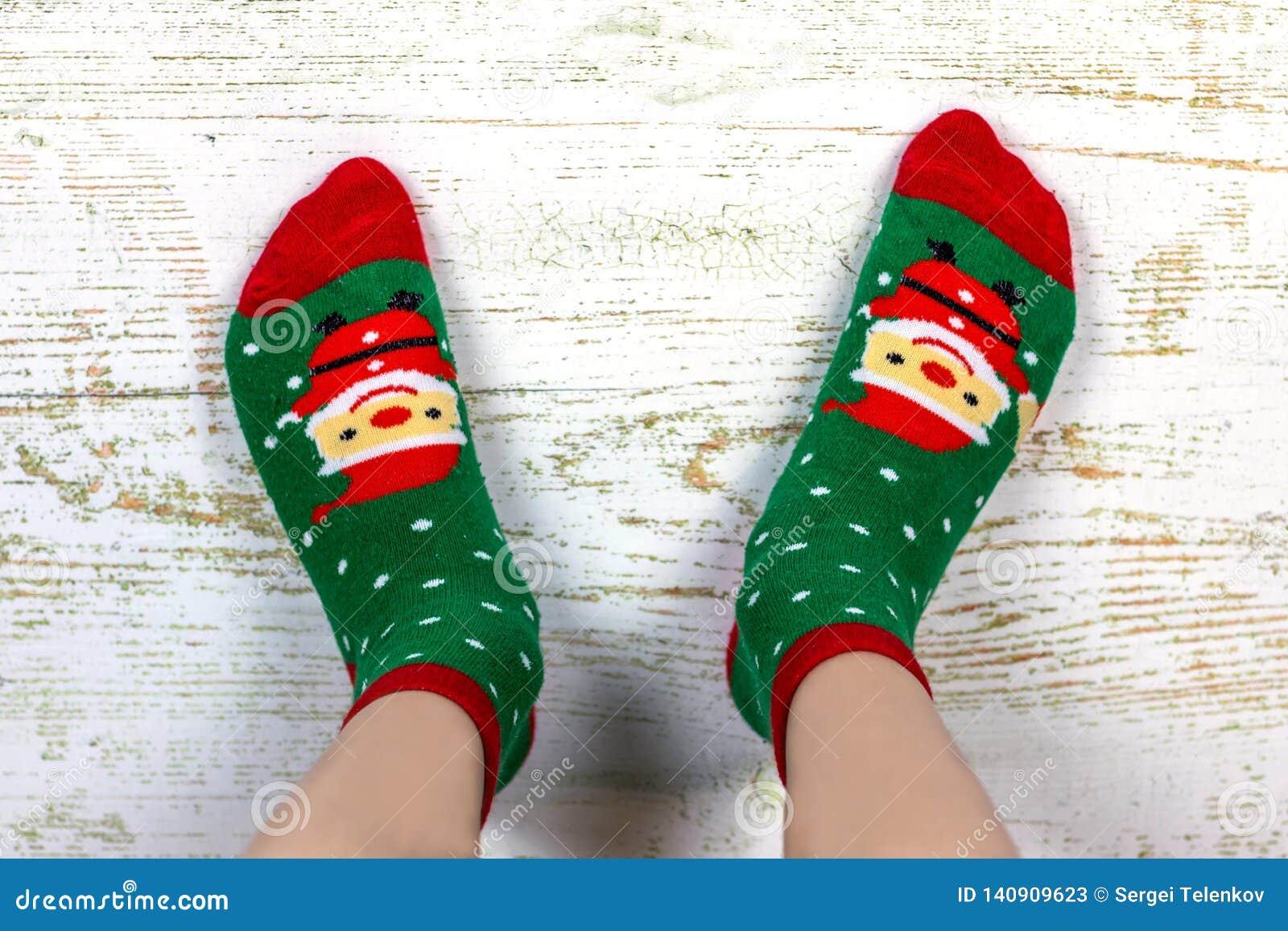 Feriado feliz Ano novo e Feliz Natal Pés do bebê em peúgas vermelhas e verdes com Santa Claus