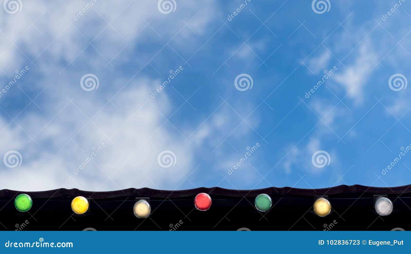 Feriado feliz, conceito do fundo da celebração do evento: linha de ampolas coloridas no beirado do telhado que olham acima, no cé