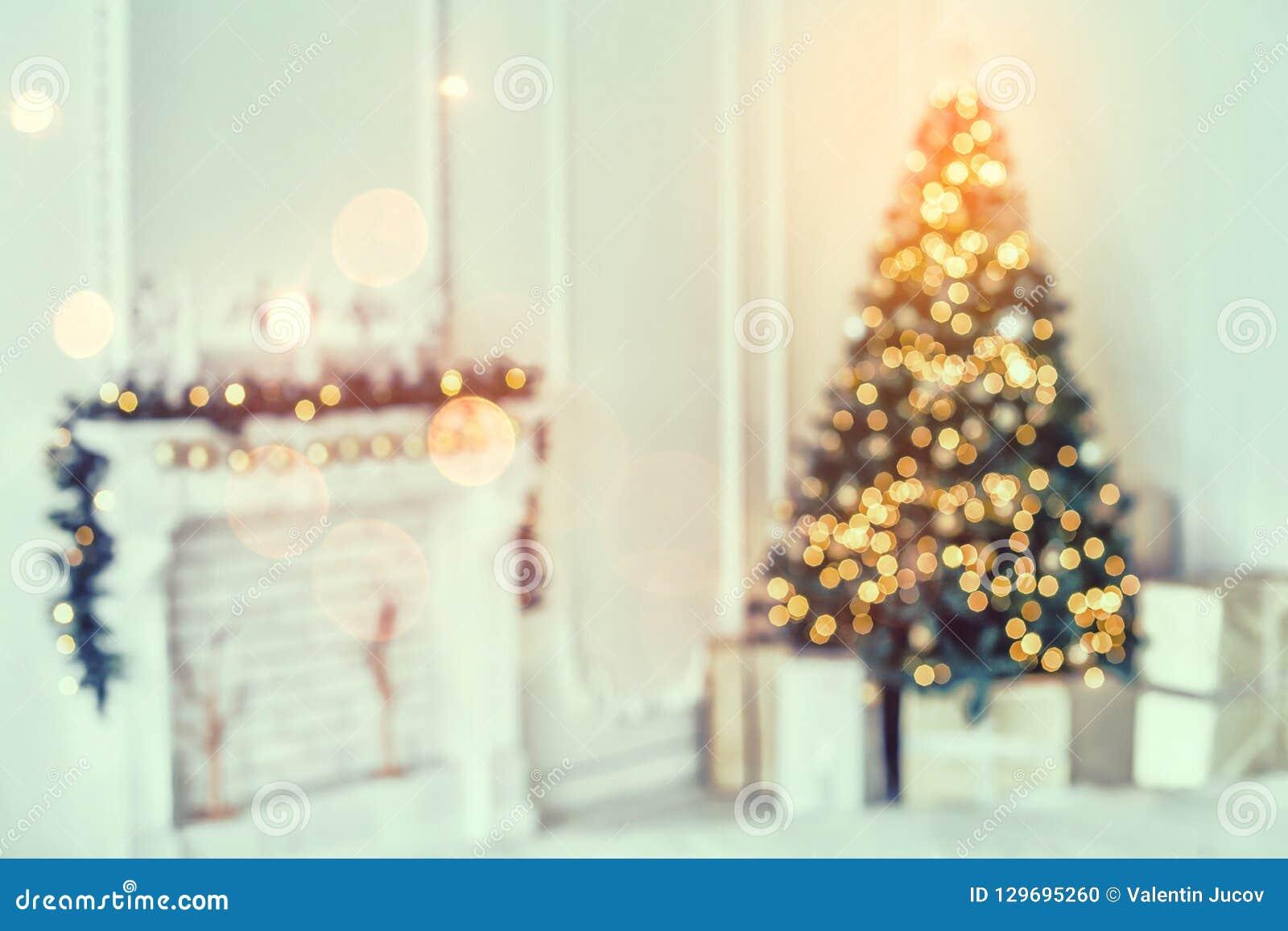 Ferie dekorerade rum med julgranen och garnering, bakgrund med suddigt och att gristra, glödande ljus