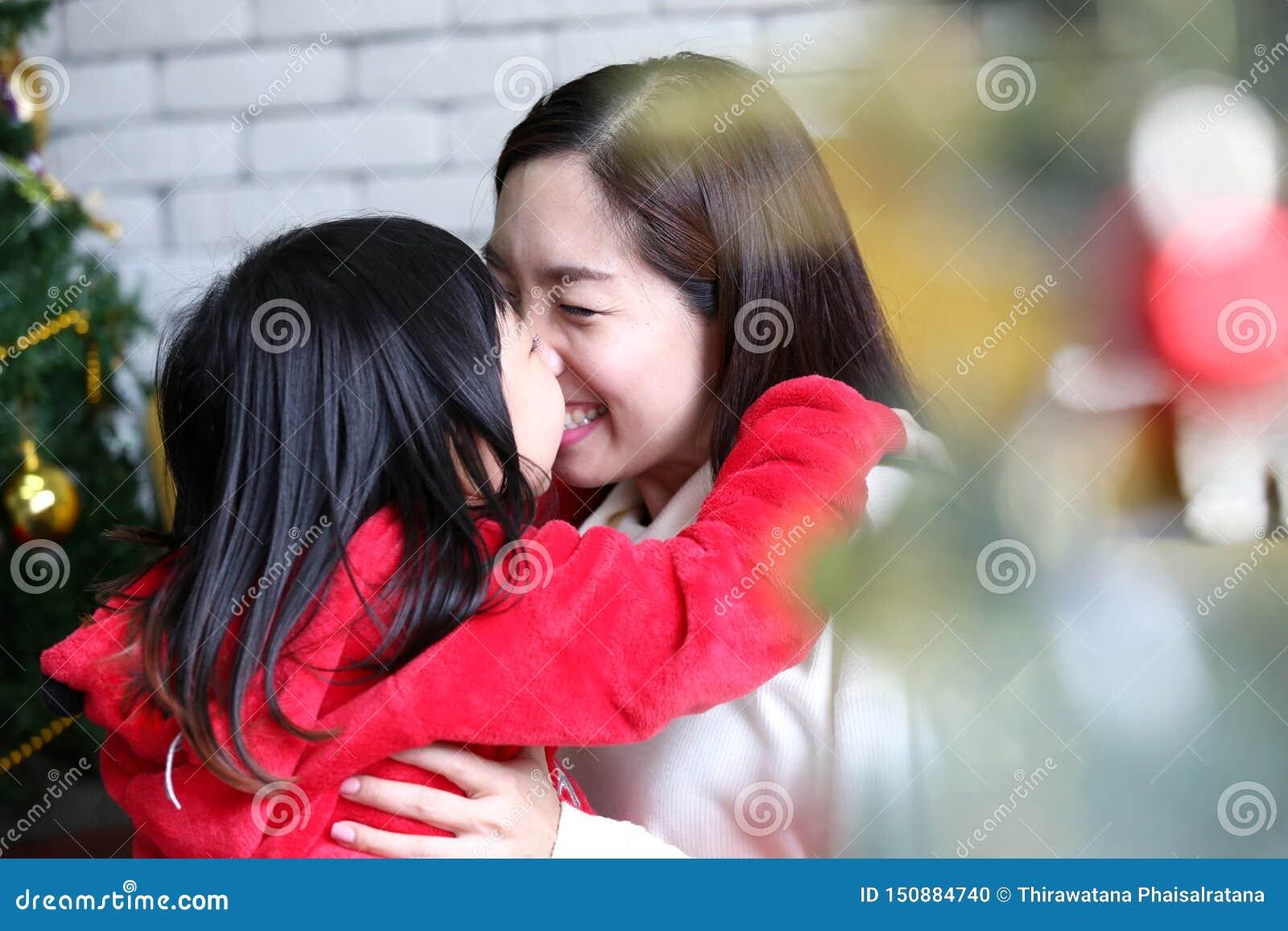 Ferie- och folkbegrepp Modern och barnet firar jul Lycklig moder och dotter som dekorerar julträdet mom