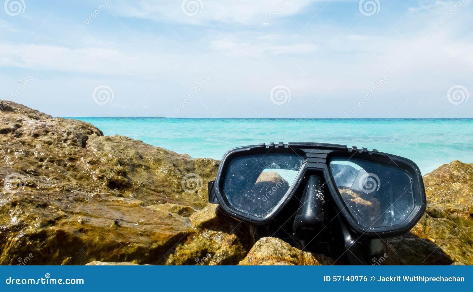 Ferien-Anfangshier Konzept, Sporttauchen-Ausrüstung auf dem weißes Seestein mit Crystal Clear Sea und Himmel im Hintergrund benut