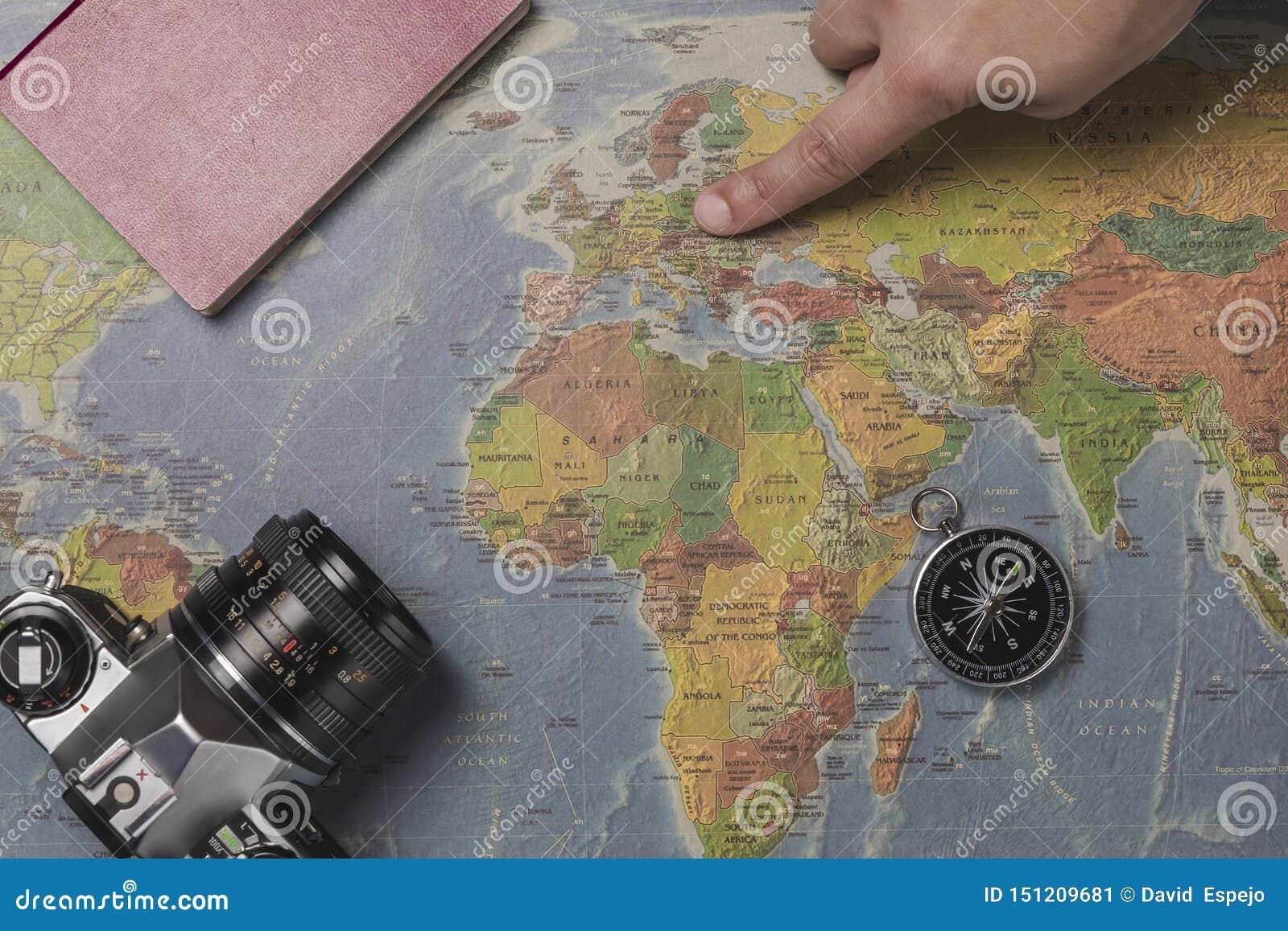 Ferien der touristischen Planung mithilfe der Weltkarte mit anderen Reisezus?tzen herum Junge Frau, die an bei Nord-Europa zeigt