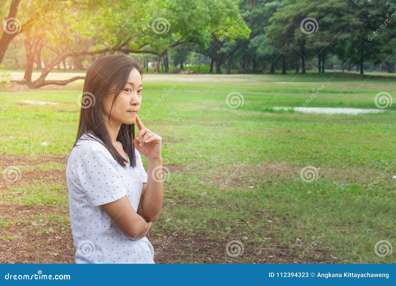 Ferien-und Feiertags-Konzept: Tragendes weißes T-Shirt der Frau Sie stehend auf grünem Gras im Park