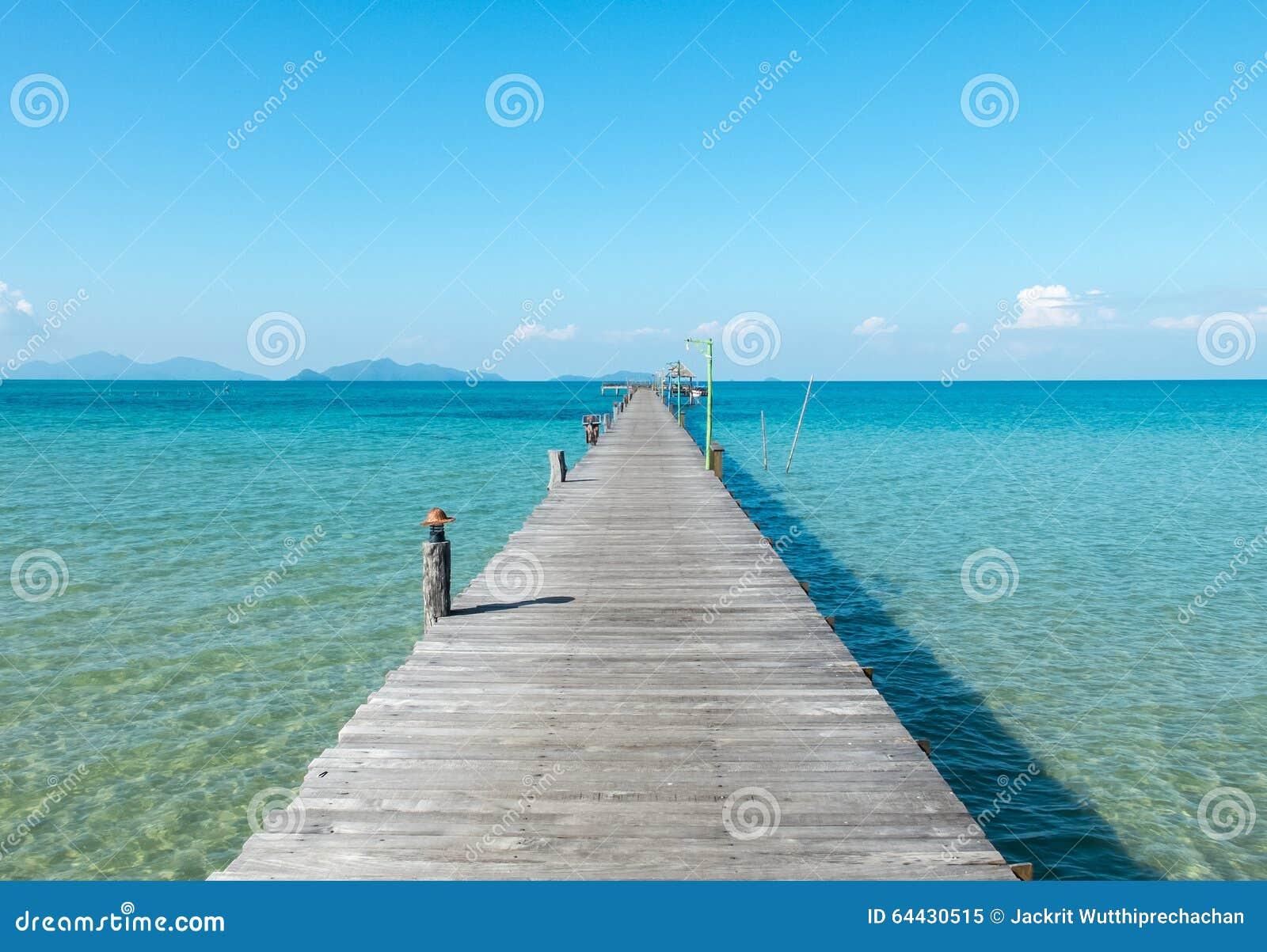 Ferien-Zeit-Konzept, hölzerner Weg zwischen Crystal Clear Blue Sea und Himmel vom Strand von Insel zum Pier in Thailand
