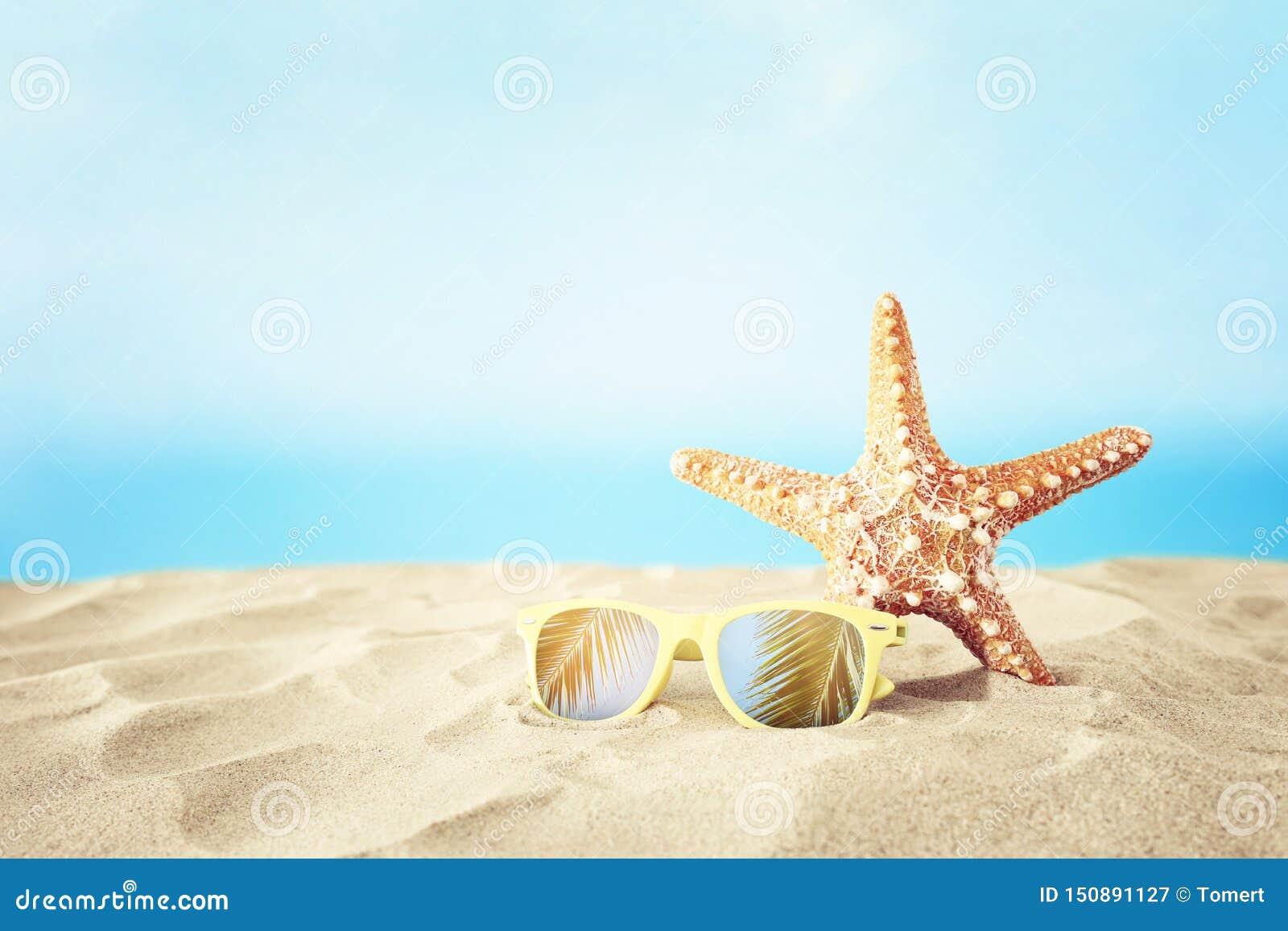 Ferier sandstrand, solglasögon och sjöstjärna framme av sommarhavsbakgrund med kopieringsutrymme