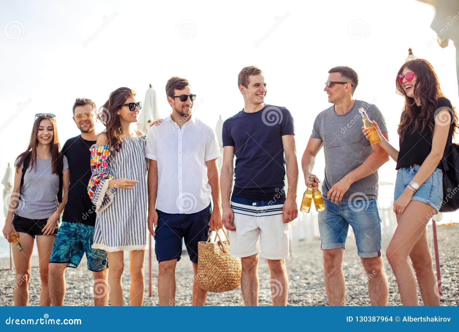 Ferier semester grupp av vänner som har gyckel på stranden, att gå, drinköl, att le och att krama
