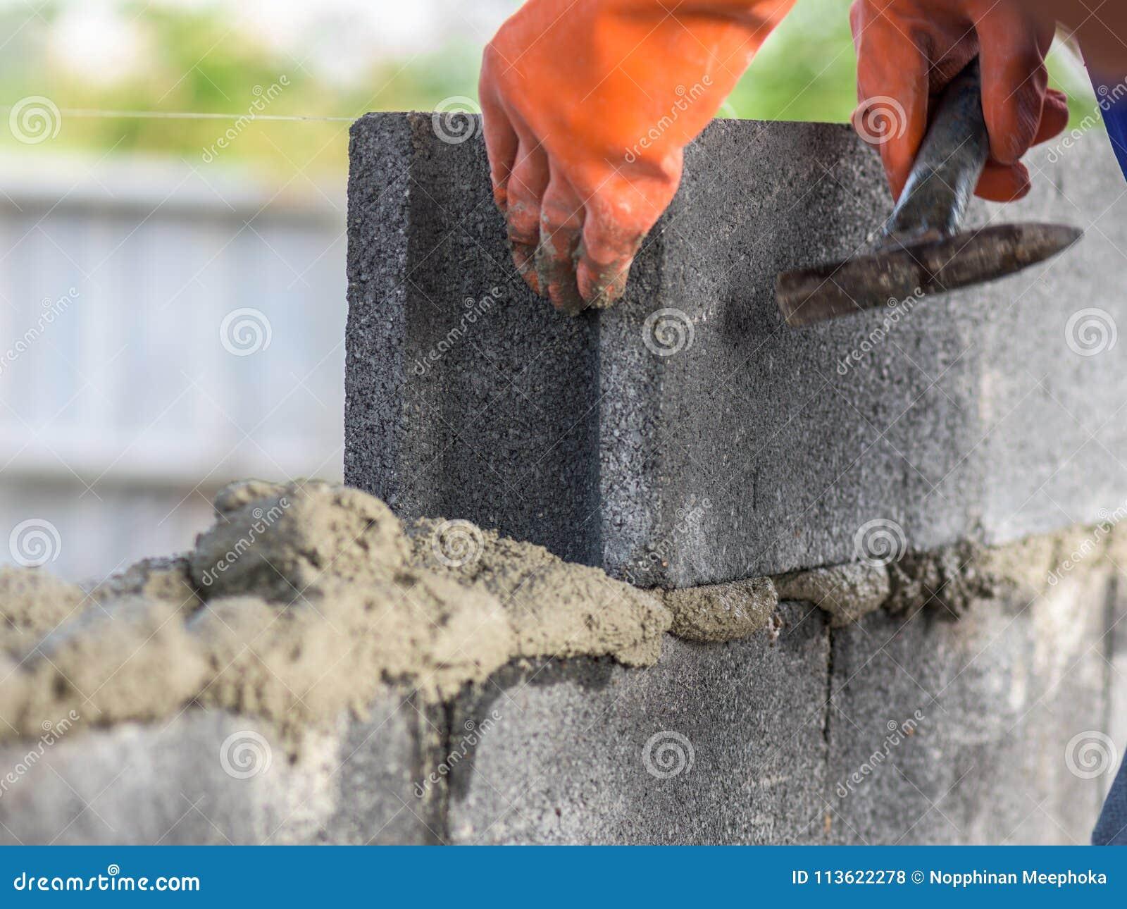 Fermez-vous d installer des briques dans le chantier de construction par le maçon industriel