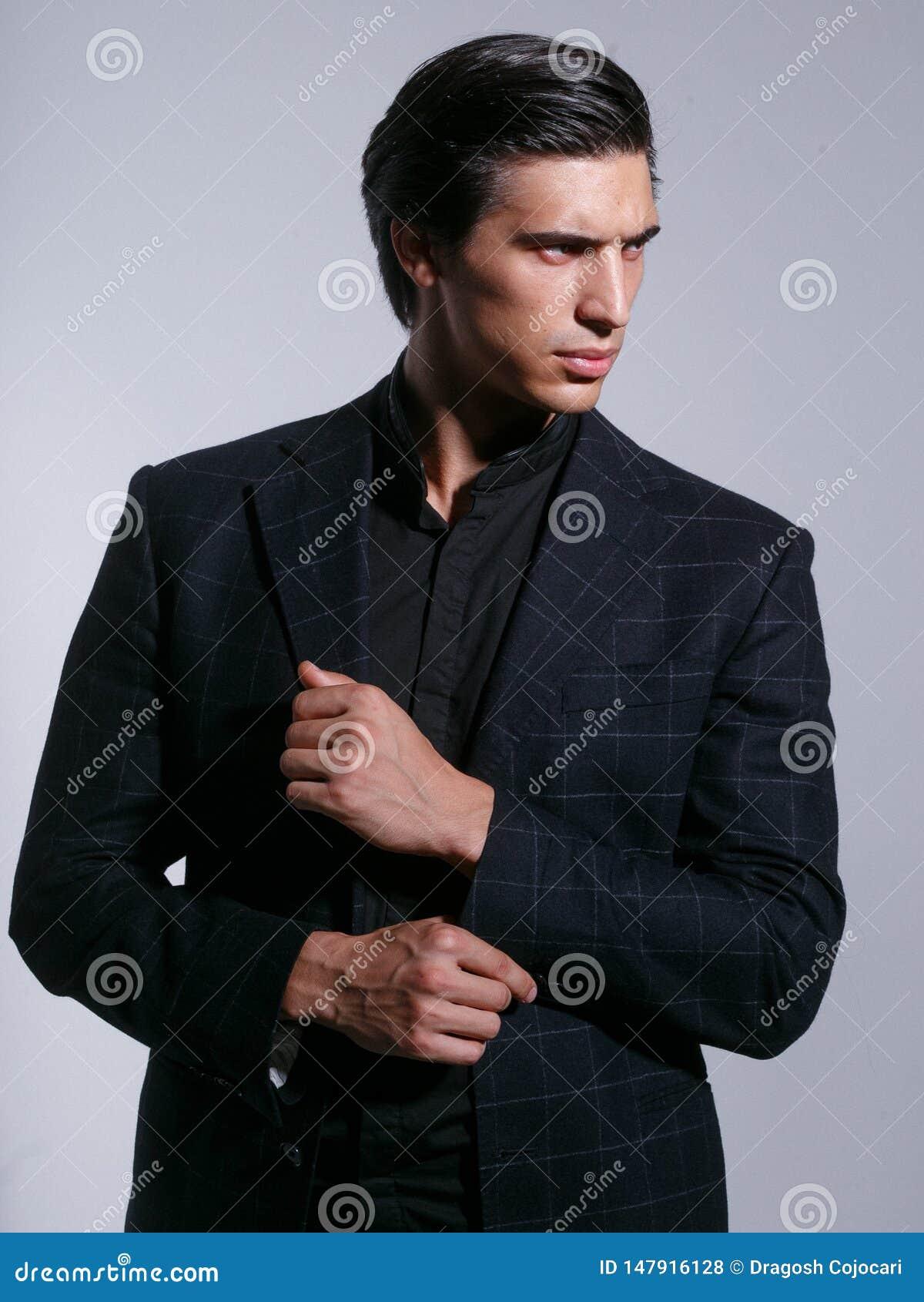 Fermez-vous d un homme brutal dans le costume élégant, posez avec l attitudine, regardant dans le profil, d isolement à un arrièr
