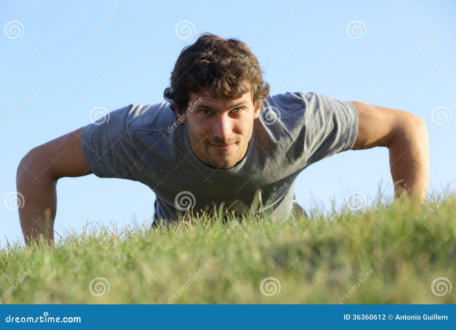 Fermez-vous d un homme faisant des pompes sur l herbe