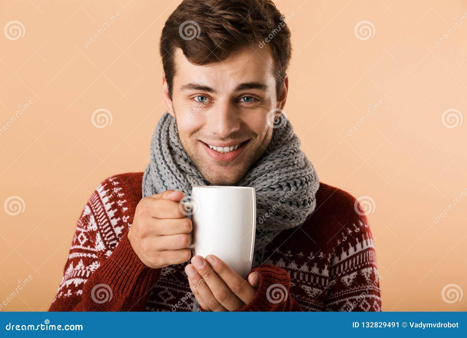 58b88bc70f71 Fermez-vous d un jeune homme de sourire habillé dans le thé potable de  chandail et d écharpe d une tasse d isolement au-dessus du fond beige