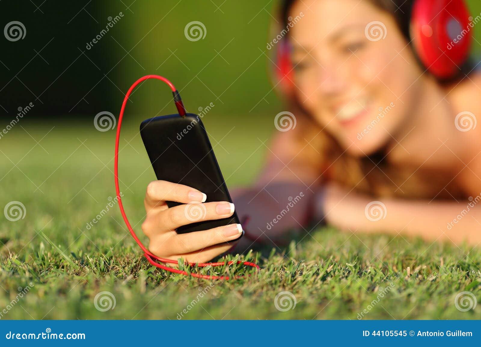 Fermez-vous d une femme avec des écouteurs tenant un téléphone intelligent