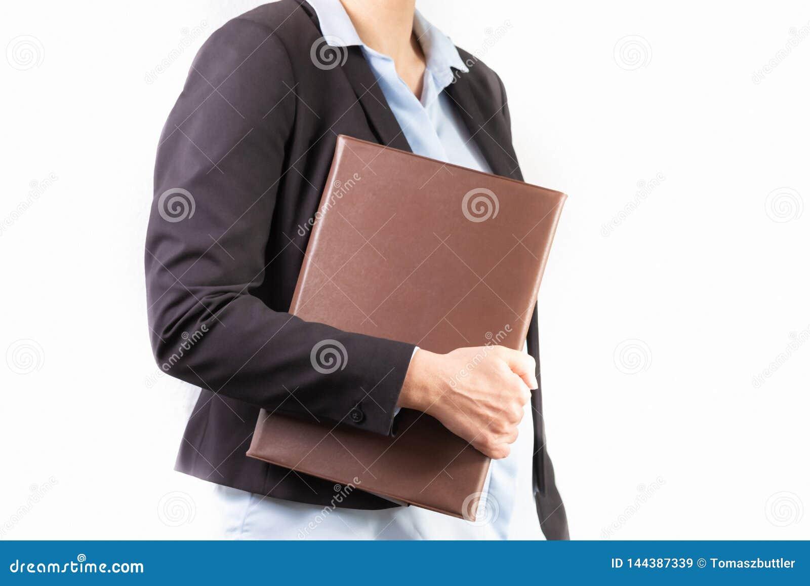 Fermez-vous d une jeune femme dans un costume tenant un dossier