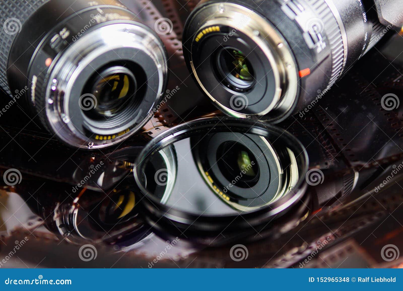Fermez-vous de deux objectifs de caméra avec le filtre circulaire d isolement sur des bandes de film négatif