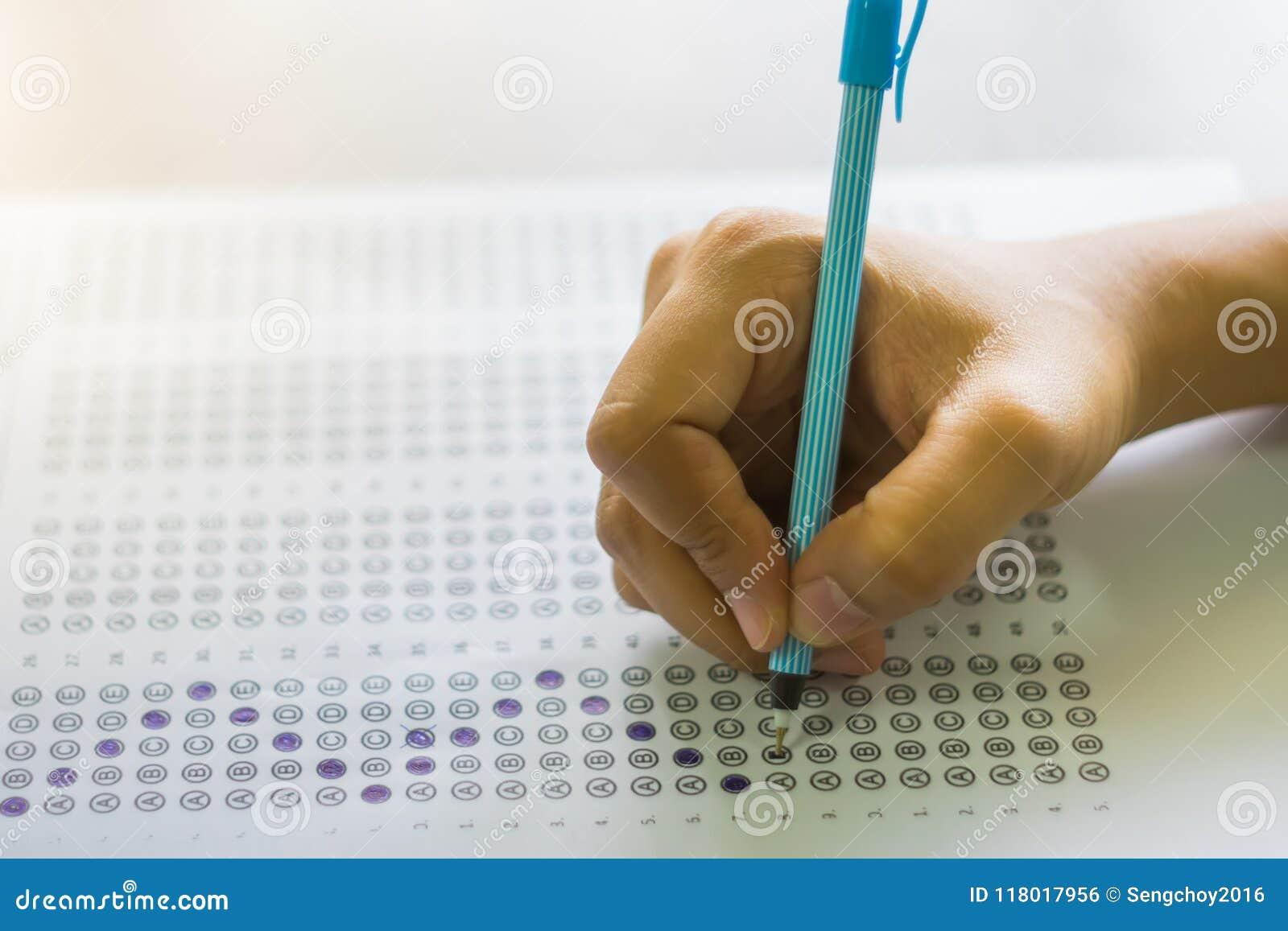 Fermez-vous de l étudiant de lycée ou tenant une écriture de stylo sur le papier de formule d utilisation dans la chambre d exame