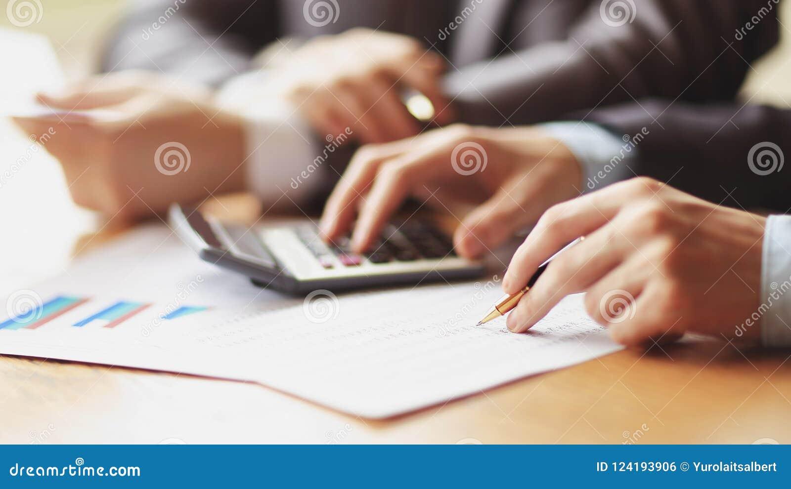 Fermez-vous de l homme d affaires ou la main de comptable tenant le crayon travaillant à la calculatrice pour calculer des donnée