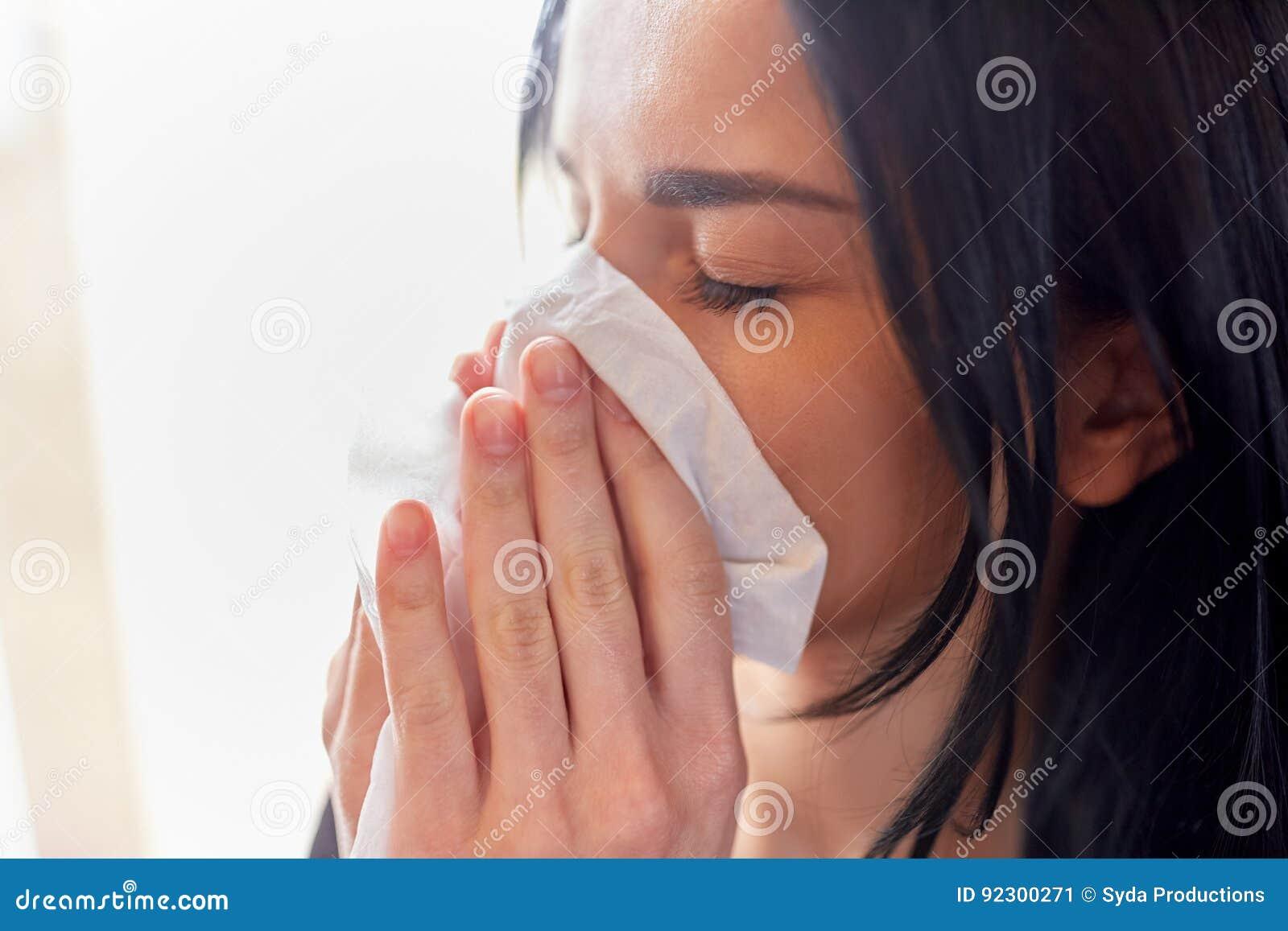 Fermez-vous de la femme avec le nez de soufflement de chiffon ou pleurer