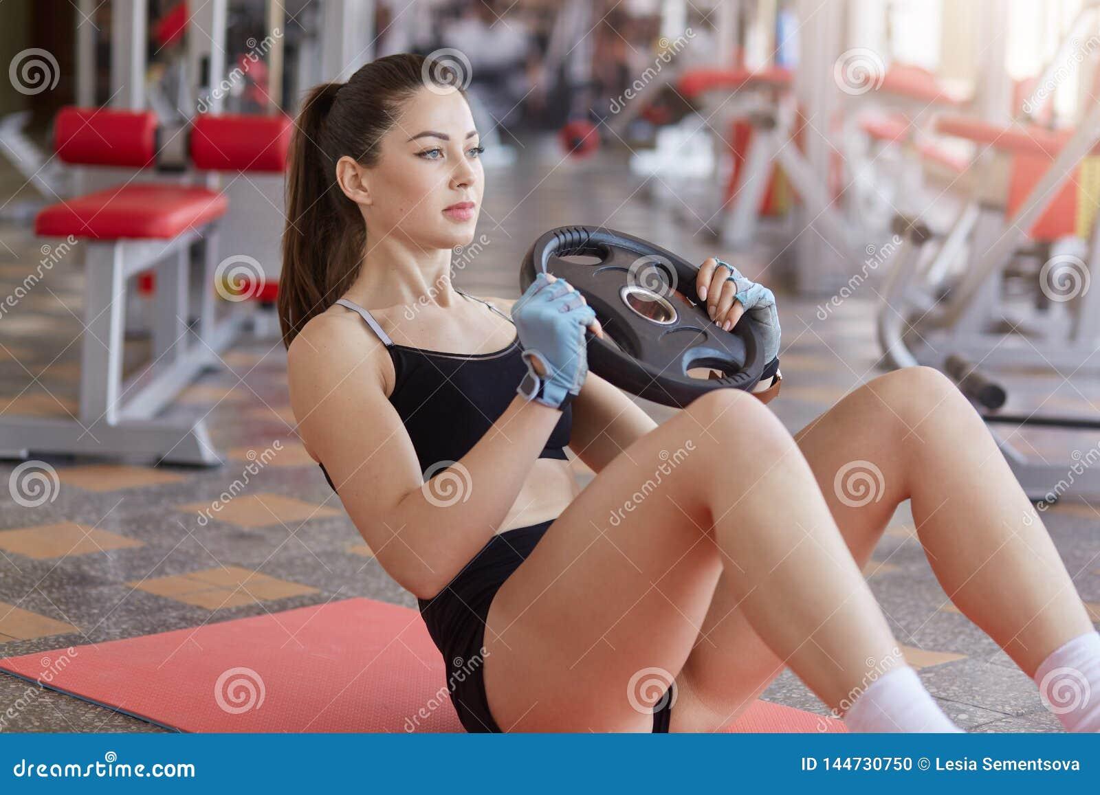 Fermez-vous de la femme faisant des exercices d ABS avec le plat de poids tout en se reposant sur le tapis de sport sur le planch