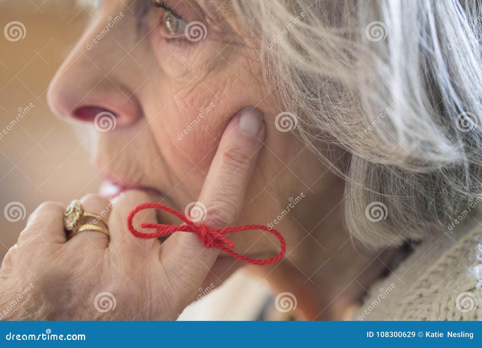 Fermez-vous de la femme supérieure avec de la ficelle attachée autour du doigt comme Remin