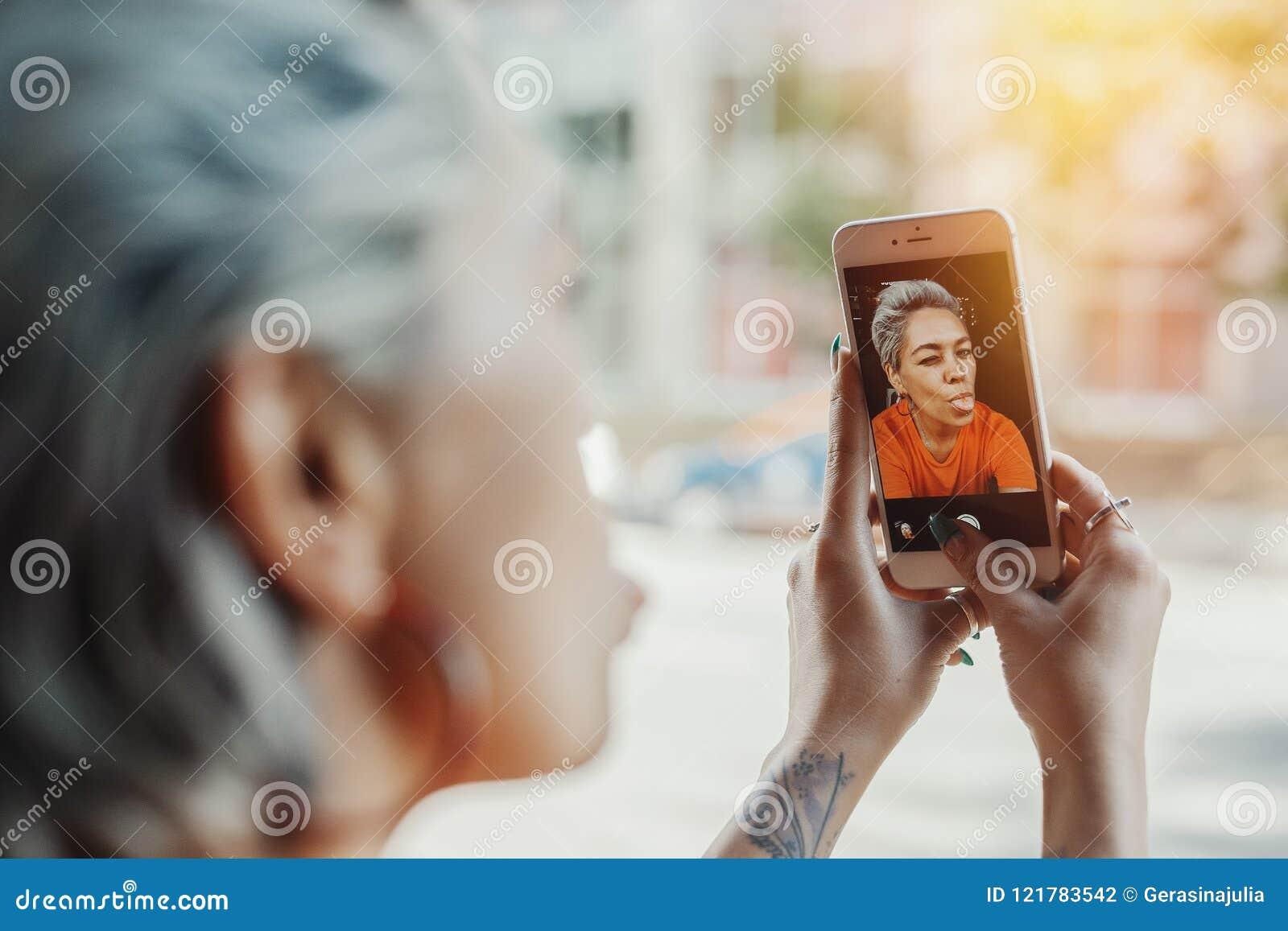 Fermez-vous de la fille blonde magnifique attirante dans le T-shirt orange faisant le selfie