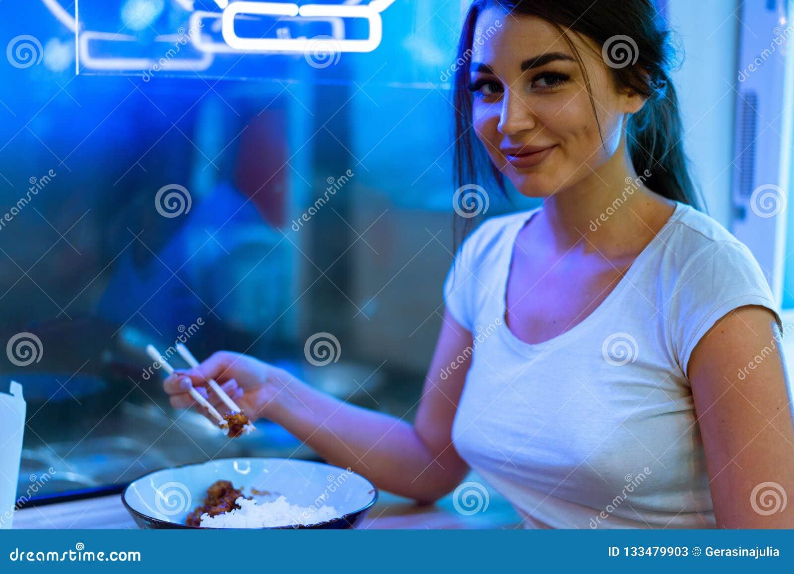 Fermez-vous de la jeune femme attirante mangeant de la nourriture asiatique avec des baguettes au café