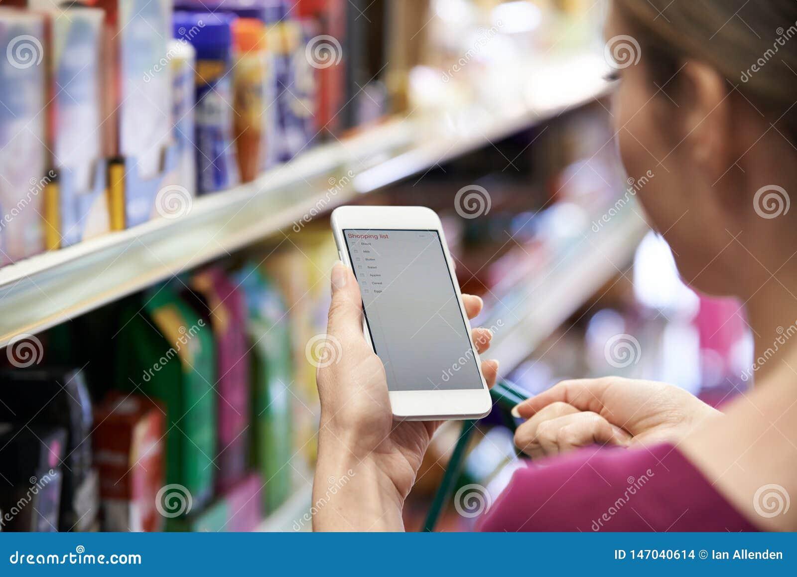 Fermez-vous de la liste d achats de lecture de femme du t?l?phone portable