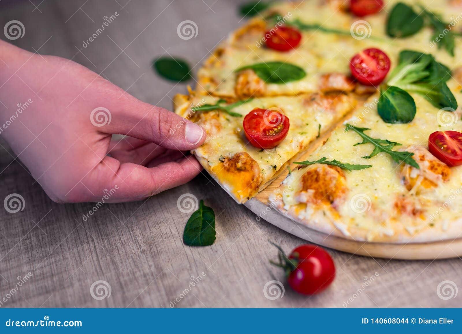 Fermez-vous de la main masculine prenant la tranche de pizza savoureuse avec des tomates et des herbes au-dessus de table en bois