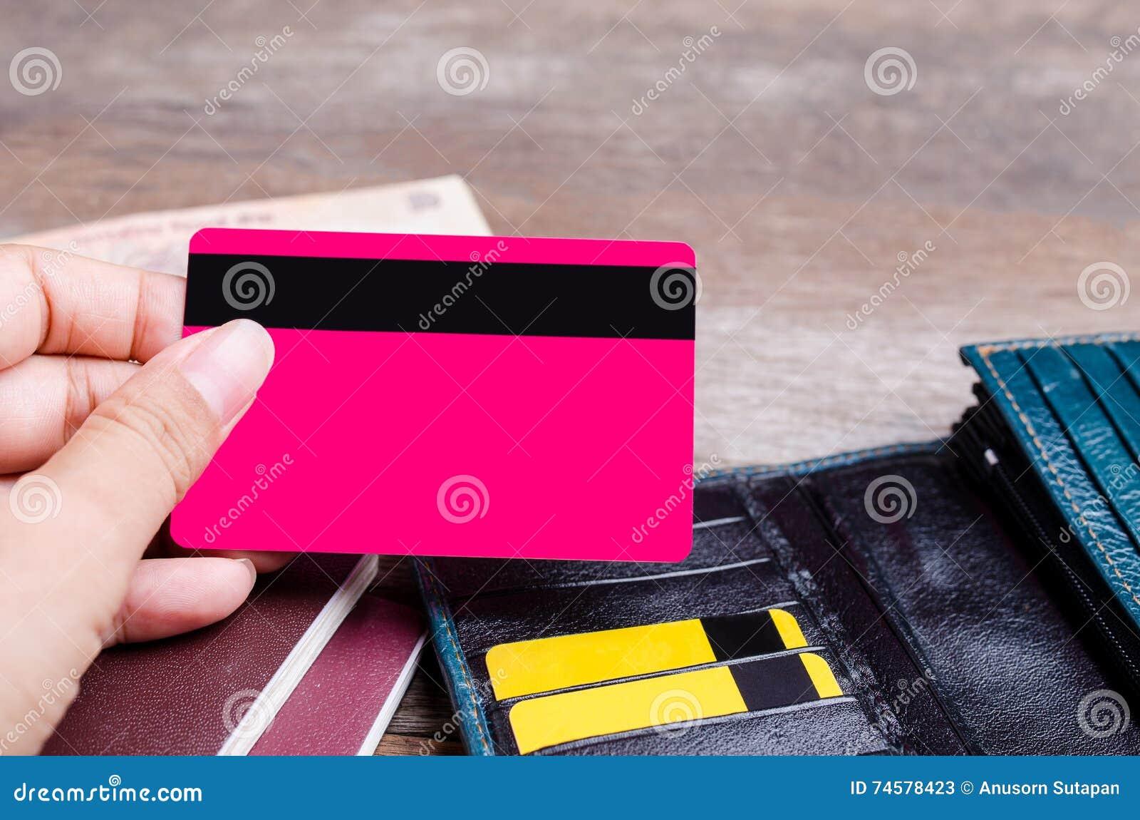 Fermez-vous de la main tenant la carte de crédit sur le fond en bois