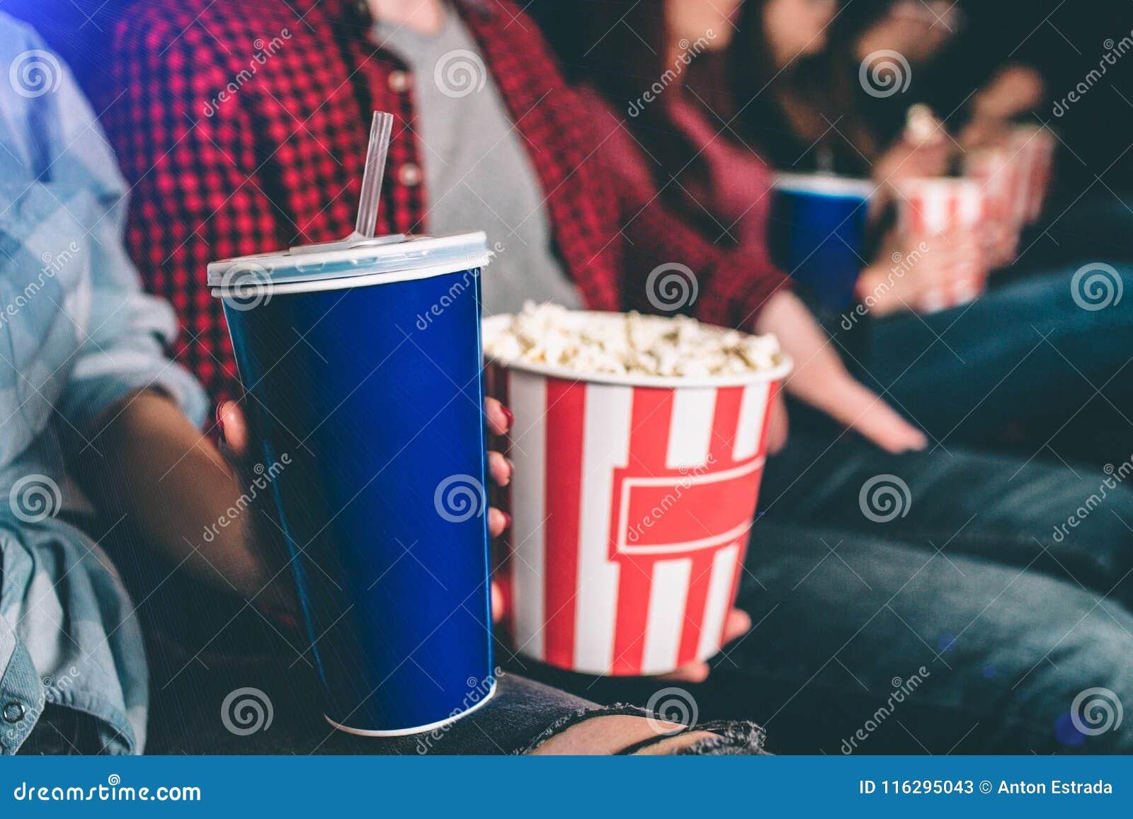 Fermez-vous de la nourriture savoureuse mais malsaine Il y a panier de maïs éclaté et une tasse bleue de coke sur la photo L homm