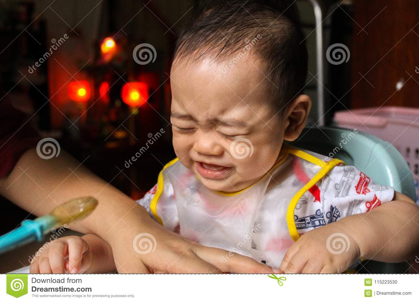 Fermez-vous de petits sept mois malheureux que le fils voient dedans le bavoir en plastique crier et pleurer dans la chaise pour