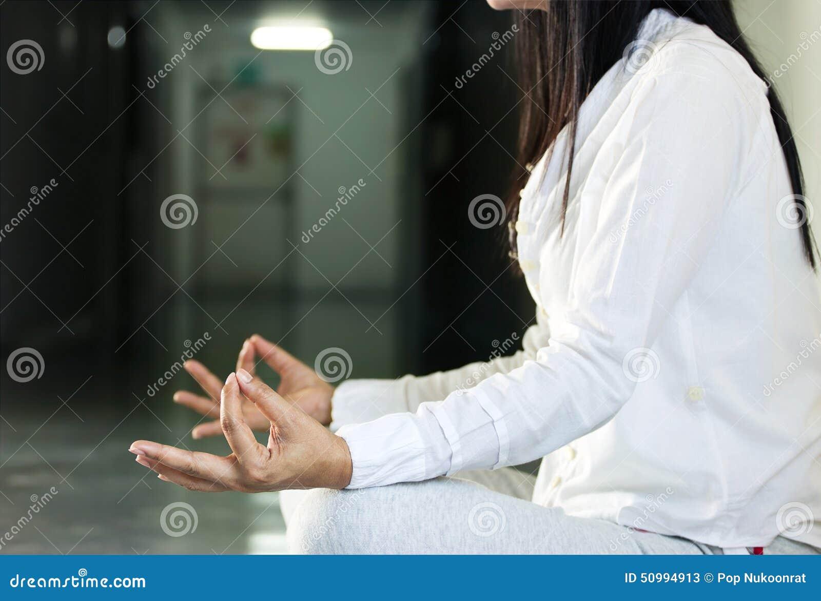 Fermez-vous de se reposer méditant de femme dans le hall