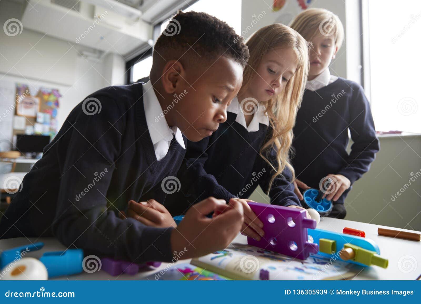 Fermez-vous de trois écoliers primaires collaborant avec des blocs de construction de jouet dans une salle de classe, angle faibl